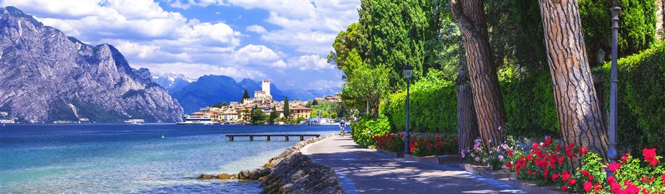 A lakeside path flanked with beautiful flowers at serena Lake Garda in Italy