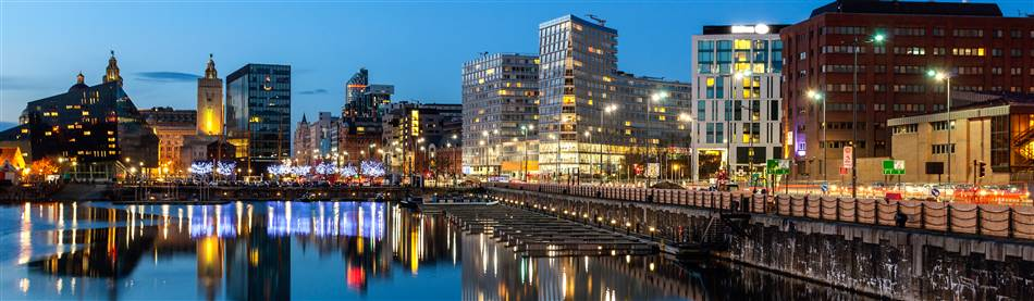 Illumintaed buildings reflecting in the waters of the Albert Docks in Liverppol on a clear evening